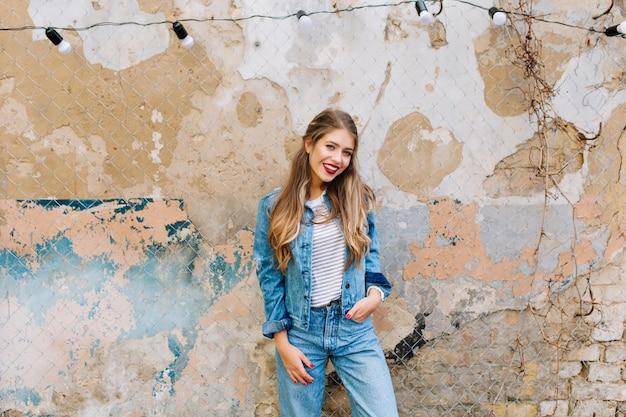 Wunderschöne junge blonde frau, die mit hand in der tasche lokalisiert auf einem schmutzhintergrund aufwirft. lächelndes hübsches mädchen mit langen haaren, die vor dem alten gebäude stehen.