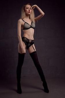Wunderschöne junge blonde frau in schöner unterwäsche und strümpfen auf dunklem hintergrund