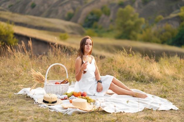 Wunderschöne junge brünette frau in einem weißen sommerkleid, das ein picknick in einem malerischen ort genießt.