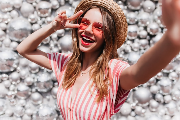 Wunderschöne junge dame in trendiger sonnenbrille, die selfie mit discokugeln macht. modisches lächelndes mädchen in gestreifter kleidung, die für sommerfest vorbereitet.