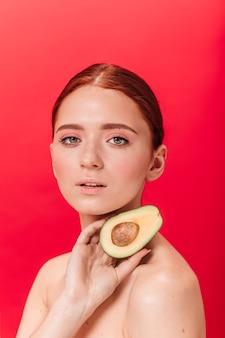 Wunderschöne junge frau, die avocado hält und kamera betrachtet. studioaufnahme des sinnlichen weiblichen modells mit ingwerhaar.