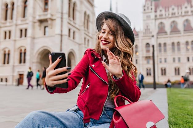 Wunderschöne junge frau, die hand auf stadtmauer während videoanruf winkt