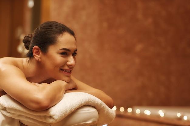 Wunderschöne junge frau, die im luxus-spa-zentrum entspannt