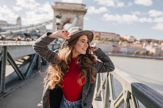 Wunderschöne junge frau, die mit aufregung während der reise in europa aufwirft
