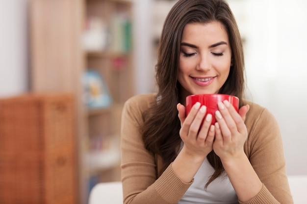 Wunderschöne junge frau, die mit tasse kaffee zu hause entspannt