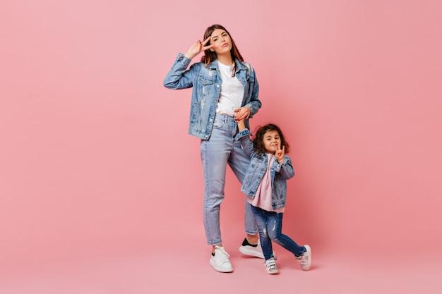Wunderschöne junge frau, die zeit mit kleiner tochter verbringt. attraktive mutter in jeans, die hände mit kind hält.