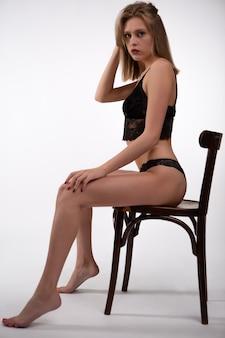 Wunderschöne junge frau in schwarzer spitzenunterwäsche, die auf einem stuhl sitzt.