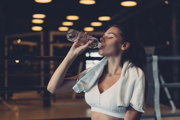 Wunderschöne junge frau mit einem handtuch auf ihren schultern trinkwasser aus einer flasche im fitnessstudio