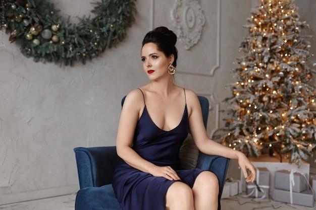 Wunderschöne junge frau mit hellem make-up und modischer frisur, die ein dunkelblaues abendkleid trägt, sitzt in einem vintage-sessel mit geschmücktem weihnachtsbaum im hintergrund.
