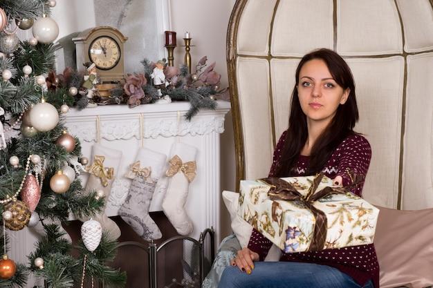 Wunderschöne junge frau mit neutralem gesichtsausdruck beim angebot von weihnachtsgeschenkschild in der nähe von kaminwand und geschmücktem weihnachtsbaum.