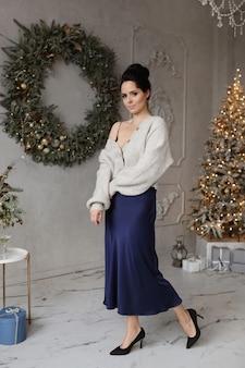 Wunderschöne junge frau mit perfektem make-up und frisur im blauen kleid und gemütlicher strickjacke posiert im...