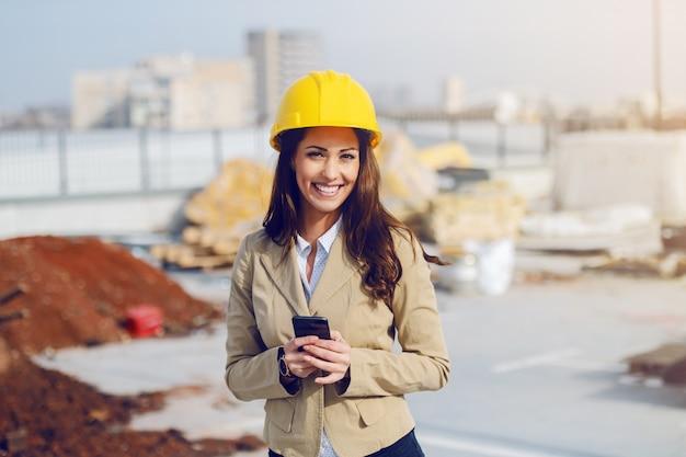 Wunderschöne kaukasische architektin in beiger jacke und mit schutzhelm beim stehen auf der baustelle und beim verwenden des smartphones.