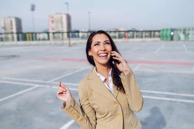 Wunderschöne kaukasische brünette in beiger jacke, die auf dem parkplatz steht und das smartphone zum anrufen des taxis verwendet.