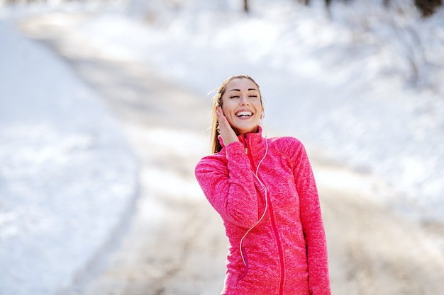 Wunderschöne kaukasische brünette mit attraktiver passform, die in sportbekleidung und mit pferdeschwanz steht und musik genießt, während sie sich nach dem laufen ausruht. winter. outdoor-fitness-konzept.