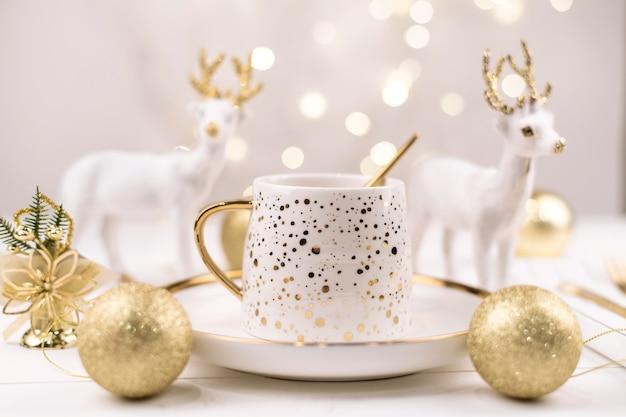 Wunderschöne komposition mit neujahrshirsch und einer weißen tasse mit einem goldenen neujahrsgetränk.