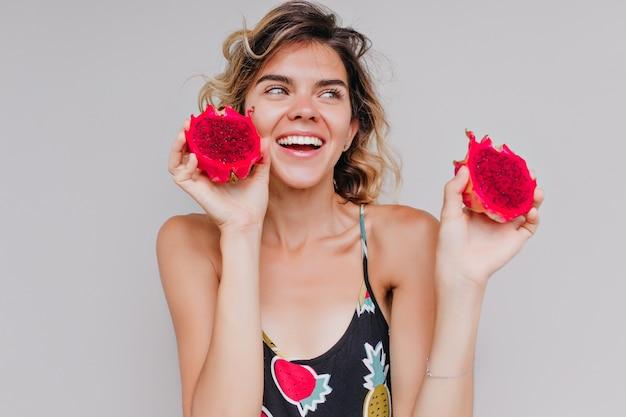 Wunderschöne kurzhaarige frau, die mit inspiriertem lächeln aufwirft und pitahaya isst. innenaufnahme der attraktiven gebräunten dame, die drachenfrüchte hält.