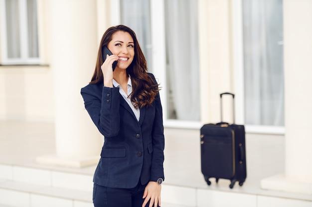 Wunderschöne lächelnde brünette gekleidet klug lässig im freien stehen und smartphone für das anrufen des taxis verwenden. im hintergrund ist ihr gepäck. geschäftsreisekonzept.