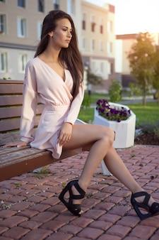 Wunderschöne lächelnde brünette in einem leichten kleid, das auf einer straßenbank sitzt