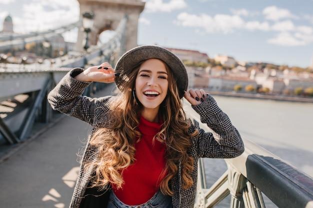 Wunderschöne lächelnde frau mit dem langen lockigen haar, das mit vergnügen auf brücke auf unschärfehintergrund aufwirft