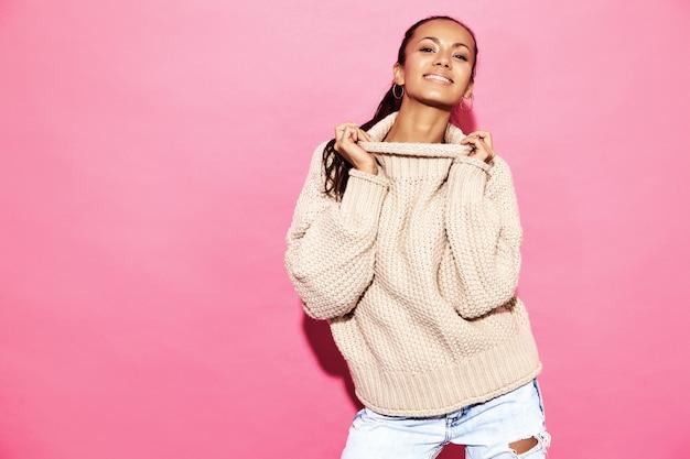 Wunderschöne lächelnde wunderschöne frau. frau, die in der stilvollen weißen strickjacke, auf rosa wand steht.