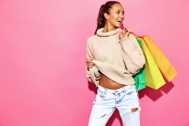 Wunderschöne lächelnde wunderschöne frau. frau, die in der stilvollen weißen strickjacke steht und einkaufstaschen, auf rosa wand hält.