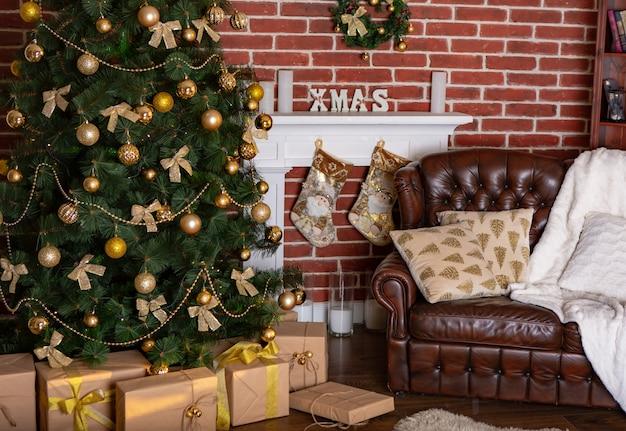 Wunderschöne lage mit einem dekorativen kamin und geschenken unter dem weihnachtsbaum und einem ledersessel mit kissen im zimmer
