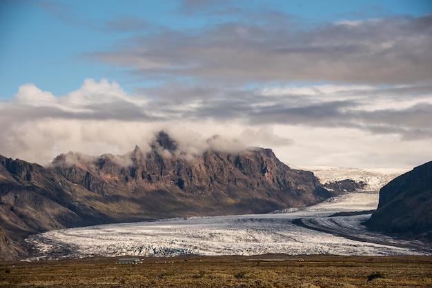 Wunderschöne landschaft der gletscher islands unter wunderschönen weißen flauschigen wolken