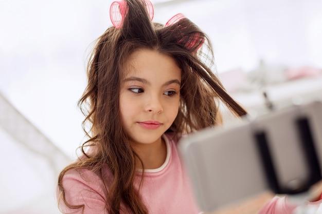 Wunderschöne locken. nettes jugendliches mädchen, das ihr haar mit hilfe von lockenwicklern kräuselt und es auf ihrem telefon aufzeichnet und dabei ist, ein video-tutorial zu veröffentlichen
