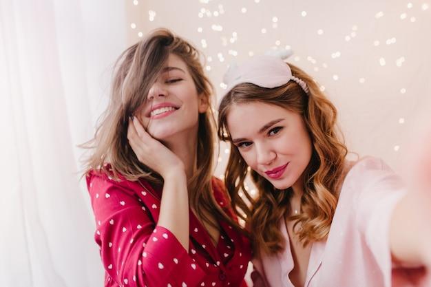 Wunderschöne lockige frau in der schlafmaske, die am morgen mit schwester selfie macht. erstaunliches brünettes mädchen im roten pyjama lächelnd, während ihr freund fotografiert.