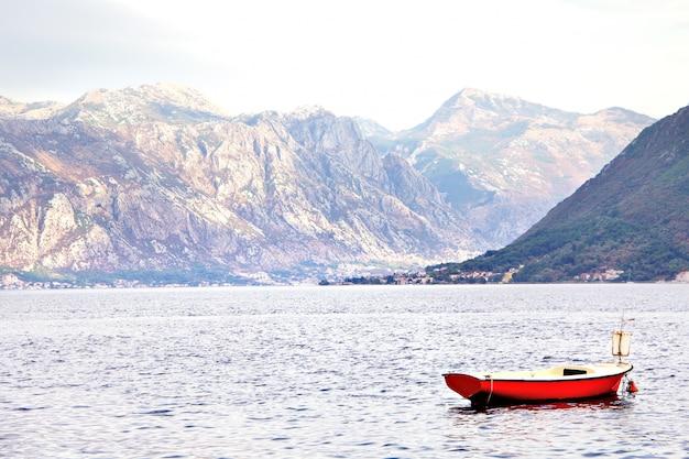 Wunderschöne mediterrane landschaft. berge und fischerboote nahe stadt perast, kotor-bucht (boka kotorska), montenegro.