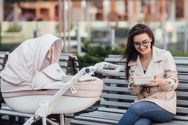 Wunderschöne mutter, die eine plastik-lunchbox hält, während sie mit kinderwagen und neugeborenen auf der bank sitzt.