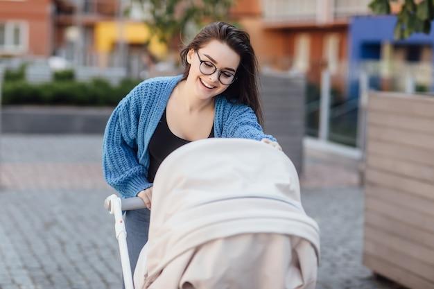 Wunderschöne mutter mit kinderwagen geht in der nähe des parks durch. spaziergang mit einem kleinkind im freien.