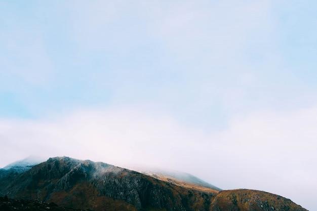 Wunderschöne nebellandschaft, die die berge bedeckt - ideal für eine tapete