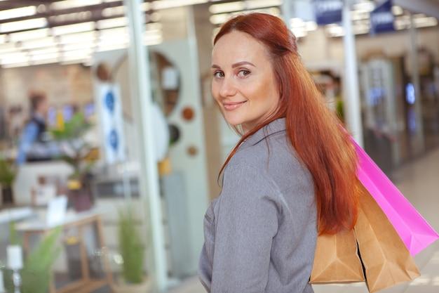 Wunderschöne rothaarige frau, die in die kamera lächelt und einkaufstaschen im einkaufszentrum trägt