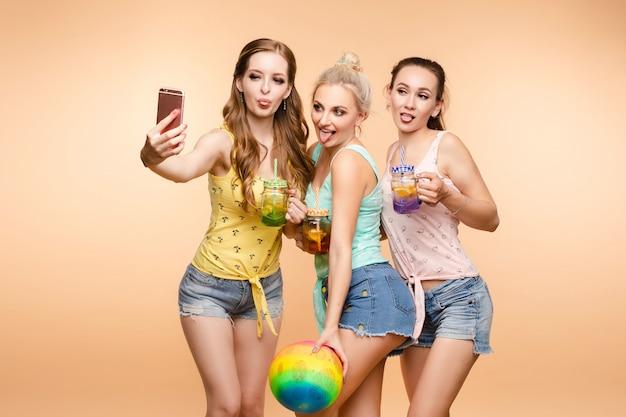 Wunderschöne schlanke freunde mit frischen sommergetränken, die selfies per handy aufnehmen.