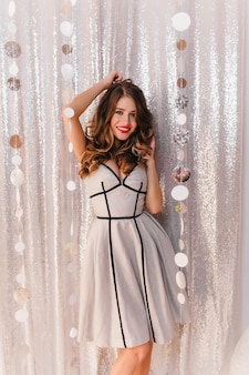 Wunderschöne, schöne frau mit schönen haaren und make-up im eleganten neujahrskleid posiert. foto in voller länge auf glänzender wand