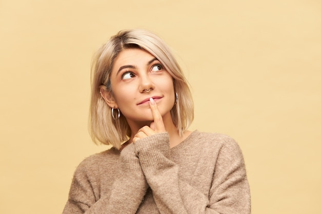 Wunderschöne schöne junge frau gekleidet in übergroßem kaschmirpullover mit neugierigem interessiertem gesichtsausdruck, der aufblickt, vorderfinger auf ihrer lippe hält und lächelt. körpersprache