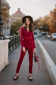 Wunderschöne schöne stilvolle frau im lila anzug, die in der stadtstraße, frühlingssommer-herbstsaison-modetrend trägt hut trägt und geldbörse hält