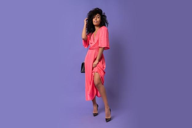 Wunderschöne schwarze frau im rosa partykleid, das über lila wand aufwirft. absätze tragen. volle länge.