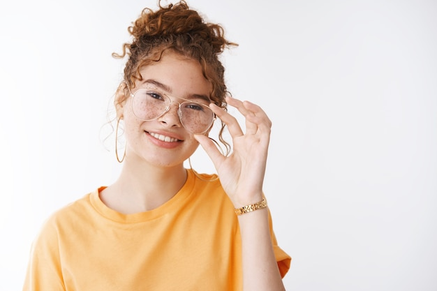 Wunderschöne sorglose europäische rothaarige weibliche unordentliche haarknoten, die eine brille berühren, den kopf kippen, glücklich lächeln, sich mit einem freund unterhalten, der sich freudig fühlt, eine positive, verspielte atmosphäre ausdrückt und selbstbewusst steht