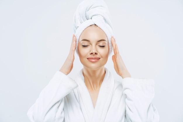 Wunderschöne spa-frau steht mit geschlossenen augen, hält hände auf handtuch auf den kopf gewickelt, in weißen bademantel gekleidet, hat gesunde haut, natürliches make-up, gepflegte hautfarbe, posiert drinnen. schönheitsbehandlung