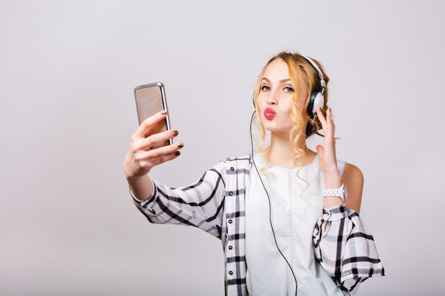 Wunderschöne süße junge frau, die selfie nahe grauer wand nimmt, smartphone betrachtet, kuss sendet. mirthful blondes mädchen, das kariertes hemd und weiße bluse trägt. fröhliche, strahlende gefühle. isoliert..