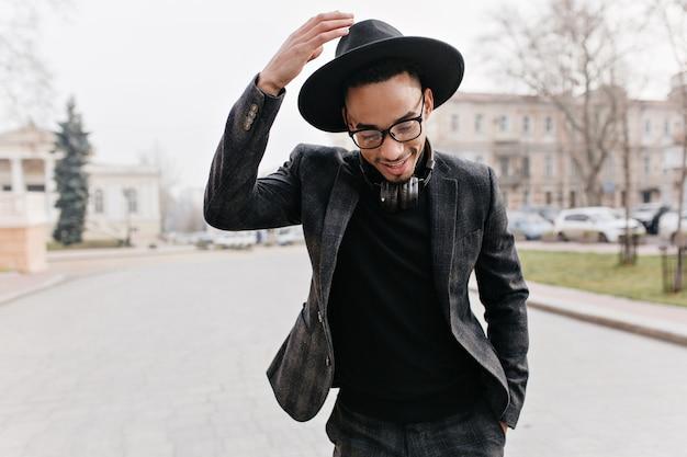 Wunderschöner afrikanischer mann, der mit schüchternem lächeln auf stadtstraße aufwirft. stilvoller schwarzer mann im hut, der auf der straße mit kopfhörern steht und lacht.