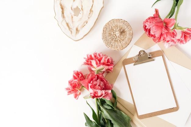Wunderschöner arbeitsbereich für den schreibtisch im home office mit frischen tulpenblumen aus rosa pfingstrosen, marmortablett, rattanschatulle, alben. flache lage, draufsicht