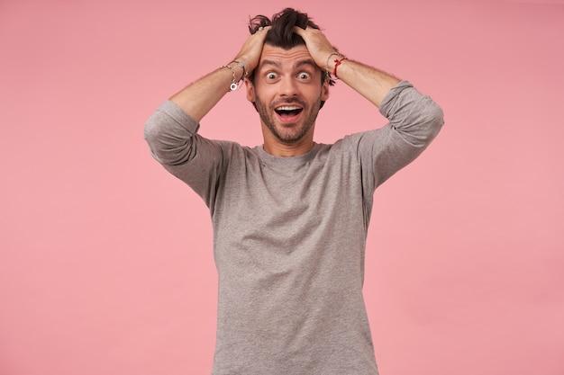 Wunderschöner bärtiger mann mit trendigem haarschnitt in freizeitkleidung, posiert mit den händen auf dem kopf und schaut mit benommenem gesicht und weit geöffnetem mund