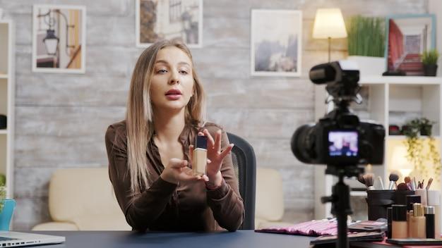Wunderschöner beauty-vlogger, der ein make-up-tutorial-produkt auf einer professionellen videokamera filmt