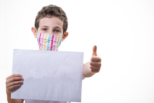 Wunderschöner brasilianischer junge, der eine maske trägt und papier für sms hält