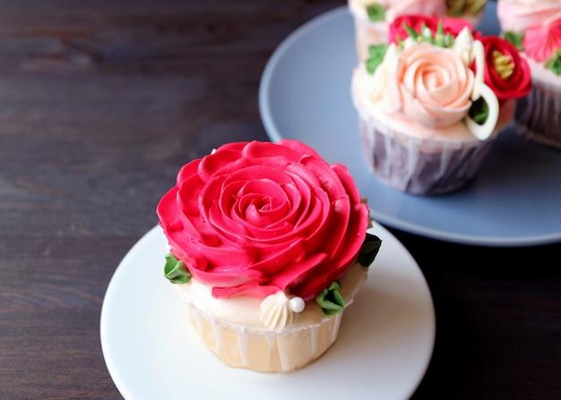 Wunderschöner cupcake mit roter rosafarbener schlagsahne