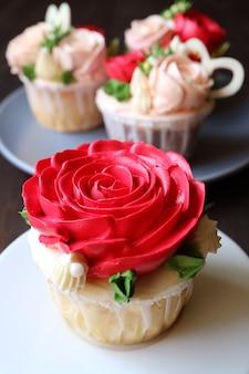 Wunderschöner cupcake mit zuckerguss der roten rose und weiteren verschwommenen cupcakes im hintergrund