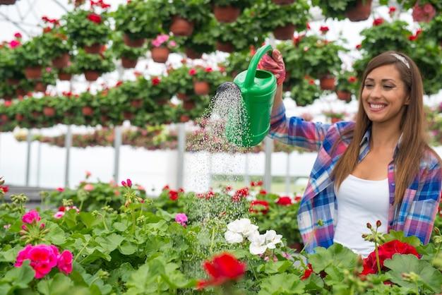 Wunderschöner florist der frau mit zahnigem lächeln auf ihrem gesicht, das pflanzen im gewächshausblumenzentrum wässert